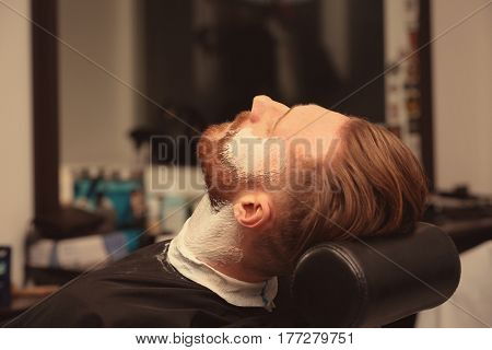 Hairdresser shaving client in barbershop