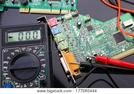 electronic boards and digital multimeter on dark background