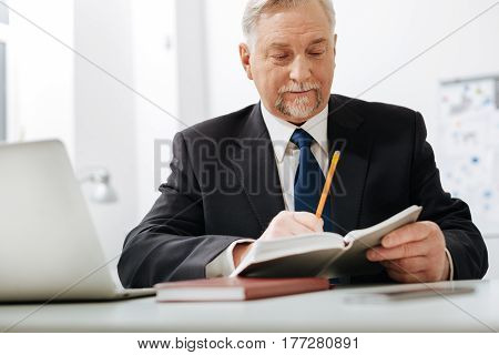 Working with papers. Punctual attentive aged employer sitting in the office while expressing concentration and checking notes in the notebook