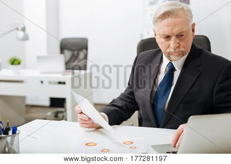 Working with important documents. Attentive thoughtful aged employer sitting in the office while expressing concentration and working with important documents