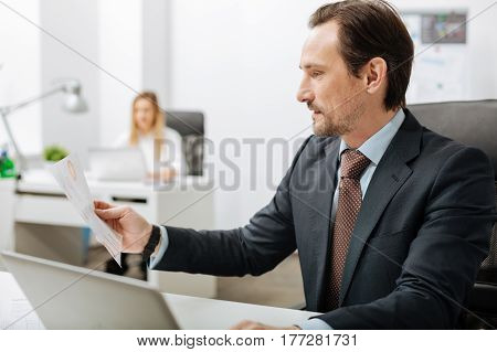 Involved in the process. Involved diligent positive executive sitting in the office and reading documents while his subordinate working in the background
