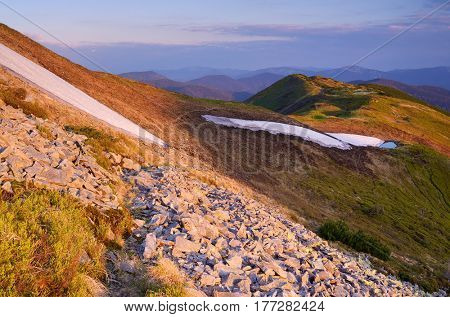 Tourist path in the mountains. Spring landscape with the last snow. Evening with a beautiful sunset