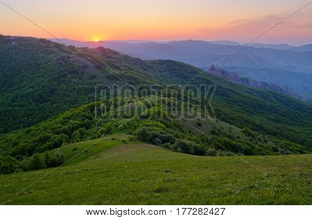 Summer landscape with a green meadow and deciduous forest in the hills. Rising sun in the mountains
