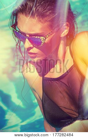 attractive  girl in bikini and sunglasses  in pool hot summer day