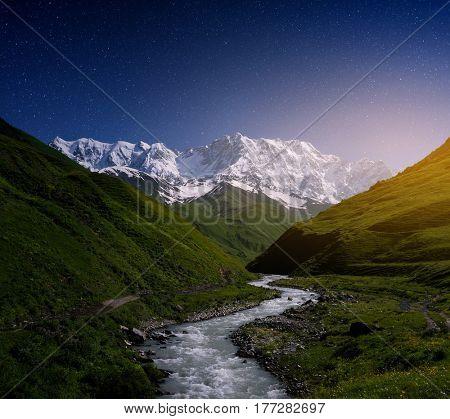 Night landscape with Enguri river. Starry sky over the mountains. Peak Shkhara, Zemo Svaneti, Georgia. Main Caucasian ridge