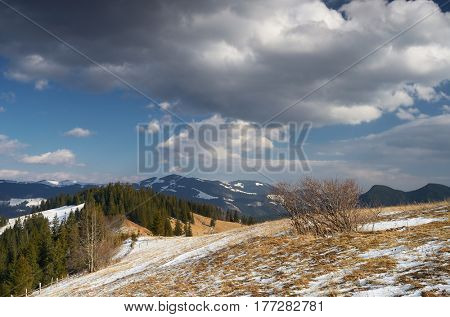 Spring landscape in the countryside. Glade with thawed snow. Beautiful sky with cumulus clouds