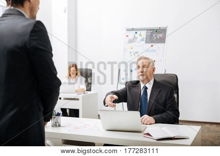 Having unpleasant conversation. Concentrated steady aged employer sitting in the office while working and having conversation with employee