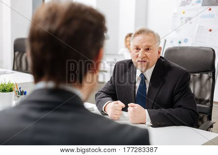 Full of wild rampage. Emotional fierce furious employer sitting in the office and having conversation with employee while expressing negative emotions and showing his fists