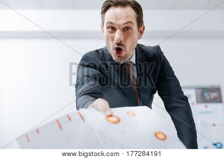 How you can be so stupid. Aggressive heated bearded businessman standing in the office and throwing away documents while expressing anger and screaming