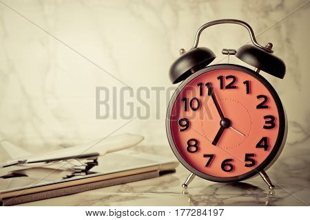 Clock timing the time to board a flight with toy plan on table with copy space