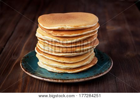 Delicious homemade pancakes on ceramic plate on wooden background