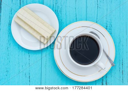 top view cup of coffee and white chocolate wafer on a blue ackground