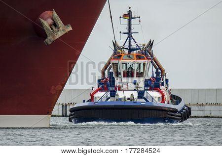 TUG - tug insures a large merchant ship