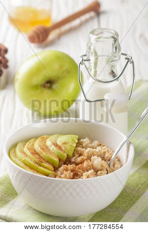 Organic Oatmeal Into A Ceramic Bowl With Apple, Cinnamon And Honey On White Wooden Table. Healthy Br