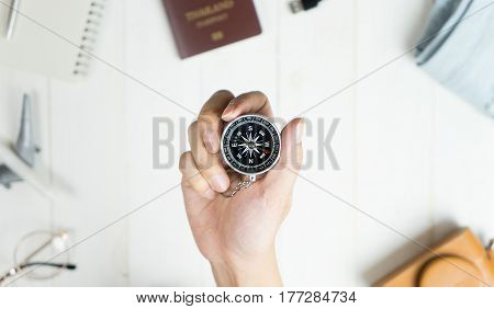 Explorer holding compass surrounded by travel accessories