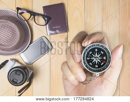 Explorer holding compass with travel accessories in background