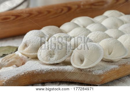 Process Of Making Homemade Raw Pastry Dumplings With Meat Filling On A Wooden Board. Pelmeni. A Trad