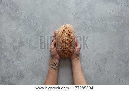 Woman holding tasty fresh bread,