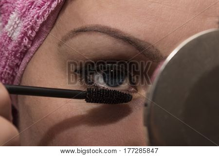 Close up photo of fashion eye makeupgirl paints eyelashes
