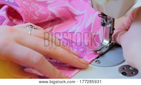 Professional tailor, fashion designer sewing clothes with sewing machine at atelier. Fashion and tailoring concept poster