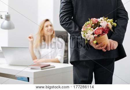 Romantic surprise. Romantic involved charismatic employee holding the bouquet while standing near the colleague and having conversation