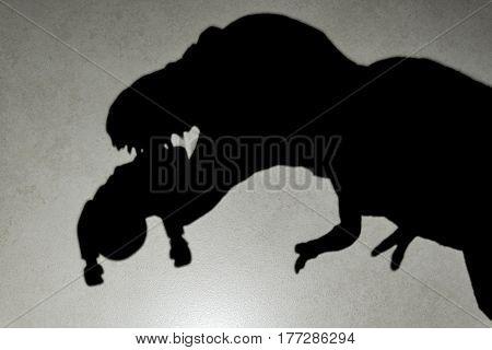 shadow of tyrannosaurus biting a body on wall close up no logo or trademark