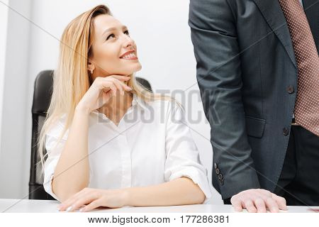 Obviously flirting with you. Charming positive smiling secretary sitting in the office while expressing charm and looking at the employer