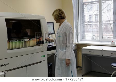 ST. PETERSBURG, RUSSIA - FEBRUARY 20, 2017: Laboratory analyst load the blood samples into the fully automated system for ID-cards in the city blood transfusion station