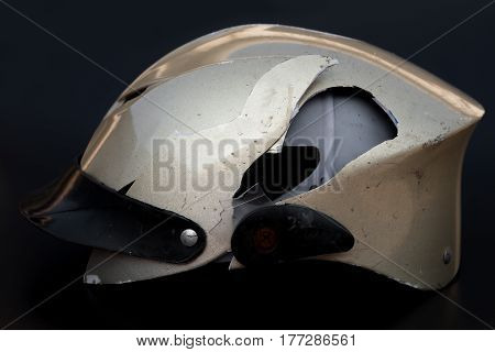 broken motobike helmet on a black background