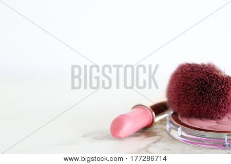 Close up elegant pink make up items frame white open space