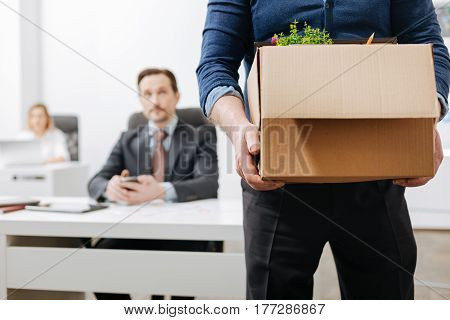 Beginning of the new life. Concentrated involved aged employee standing and holding the box with his belongings while leaving the office