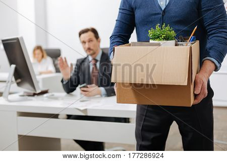 Moving to the next level. Concentrated involved senior employee standing and holding the box with his belongings while leaving the office