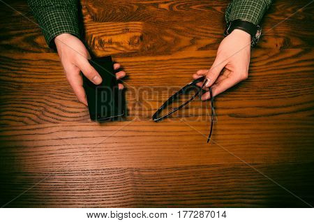 Man hand touch on a screen of mobile phone on a wooden table. Business situation. Glasses on a table