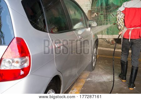 man washing a car with soapy water
