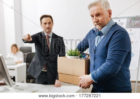 The worst staff member. Confident serious determined employer standing and pointing out while firing the employee from the job