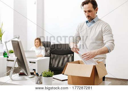 Unexpected layoff. Fired involved sad employee standing and gathering the box with his belongings while leaving the office and expressing despair