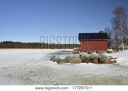 Melting sea ice in spring sun and rocks and a red boathouse in background against a blue skypicture from the North of Sweden.
