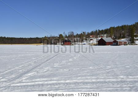 Snow and ice and snowmobile tracks and a little fishing village with red boathouses against a blue sky picture from the North of Sweden.