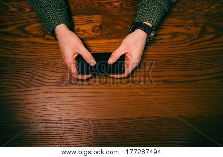 Man hand touch on a screen of mobile phone on a wooden table. Business situation.
