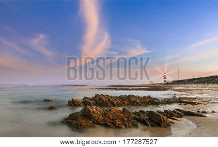 Long exposure of Lighthouse at dusk with rocks in the foreground