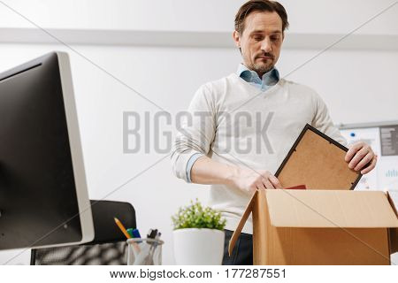Having no idea what to do . Depressed involved melancholy employee standing and packing the box with his belongings while leaving the office and expressing sadness