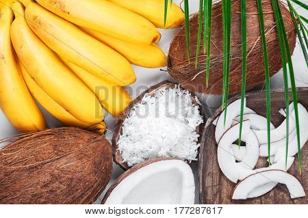 Coconuts and bananas on the white table