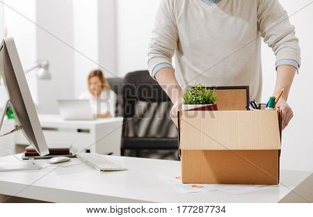 Taking a gap in my career. Concentrated involved powerful employee standing and holding the box with his belongings while leaving the company and expressing sadness