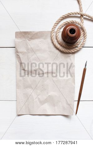 Empty Crumple Sheet Of Paper, Inkpot, Pen And Rope On The White Wooden Table