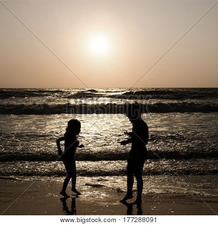 Silhouettes of children on a sea beach in India