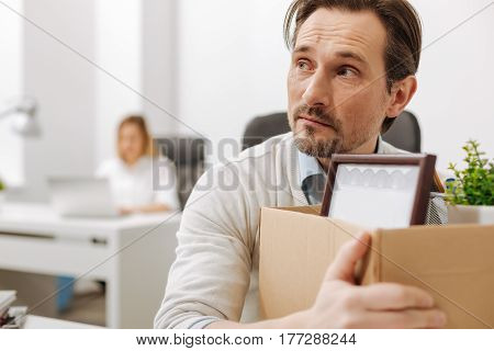 Sad atmosphere. Fired scared upset employee sitting and holding the box with his personal documents while expressing sorrow