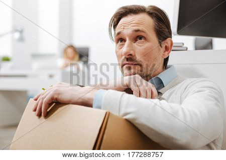 Feeling sad. Fired sad upset employee sitting on the floor and holding the box with his personal stuff while expressing sadness