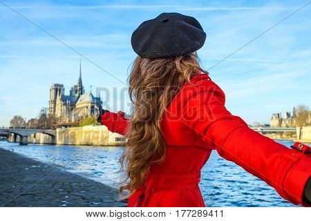 Woman Holding Friends Hand And Pointing At Notre Dame De Paris