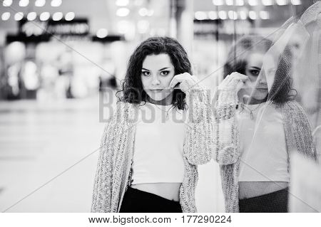 Young Curly Model Girl Posed On Mini Skirt At Large Shopping Center Near Showcase With Mannequin. Bl