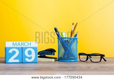 March 29th. Day 29 of month, calendar on light yellow background, workplace with office suplies. Spring time, empty space for text.
